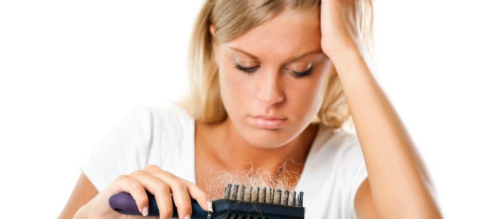 donna che osserva i capelli caduti all'interno della spazzola