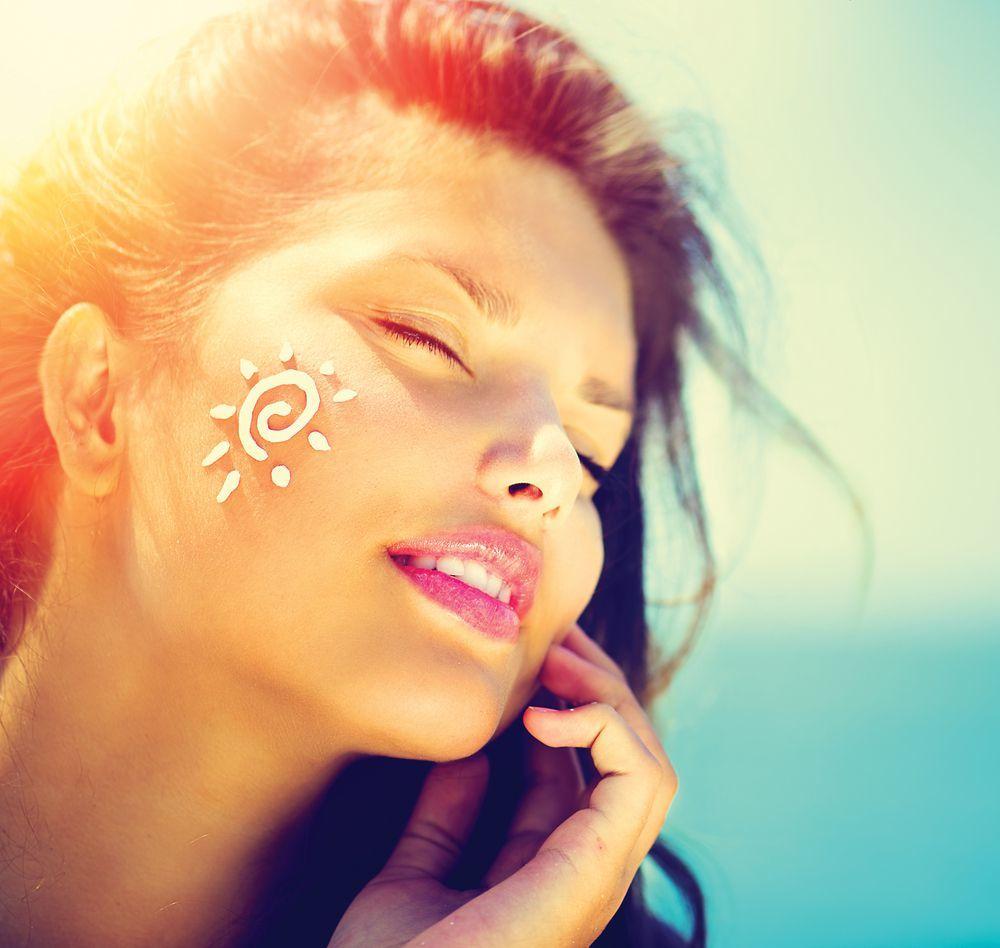 Donna con crema solare sul viso