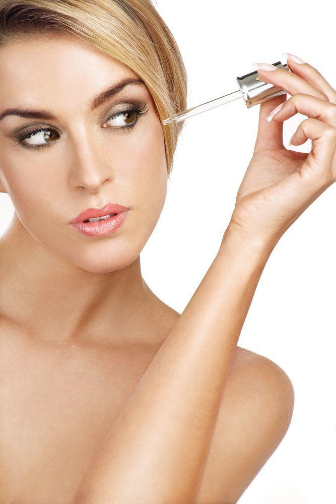 donna mentre applica sul volto il siero vitamina c