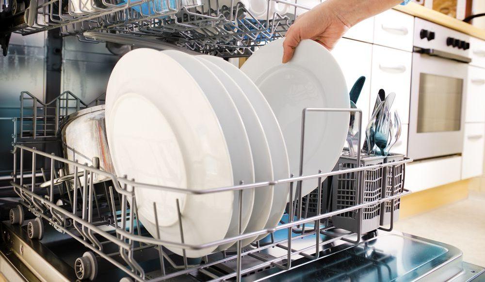 Lavastoviglie aperta con carrello estratto e piatti