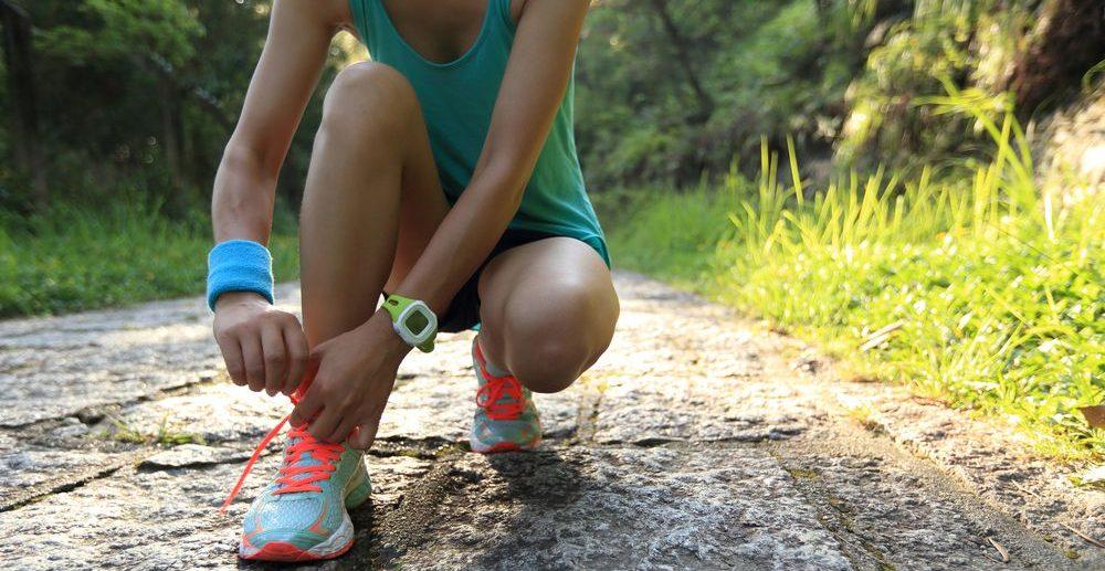 Ragazza mentre si allaccia le scarpe durante una sessione di running con focus sull'orologio sportivo