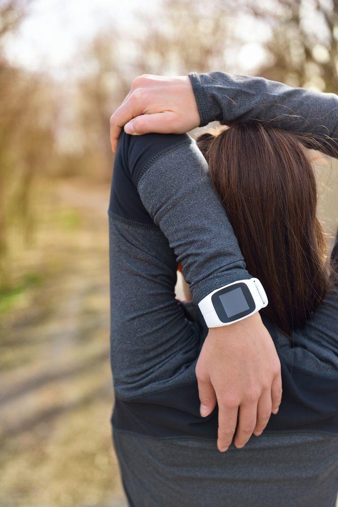 Runner donna con orologio sportivo al polso durante stretching