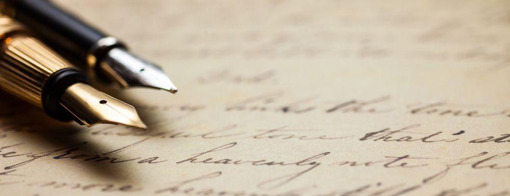 coppia di penne stilografiche su pergamena, una placcata oro e l'altra argento