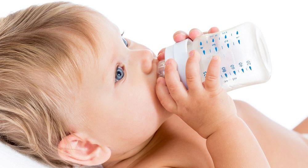 neonato mentre beve il latte dal biberon anticolica