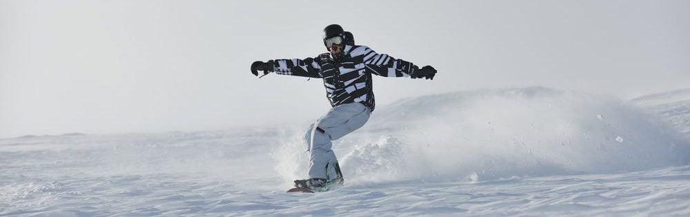 snowboarder che indossa attrezzatura completa da snow su una tavola da freestyle