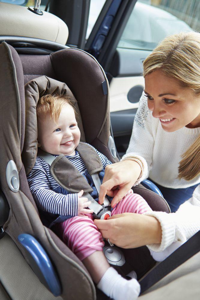 mamma che sorride al figlio mentre indossa le cinture di sicurezza al seggiolino auto