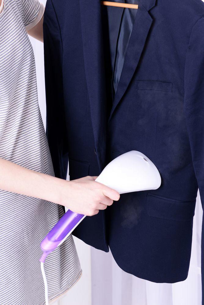 donna che usa ferro da stiro verticale su giacca