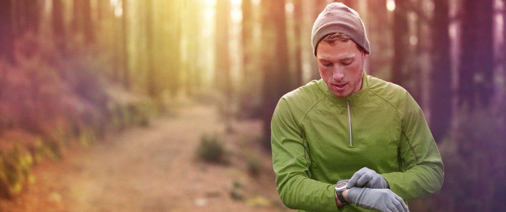 ranner in pausa dalla corsa mentre legge i dati sul cardiofrequenzimetro