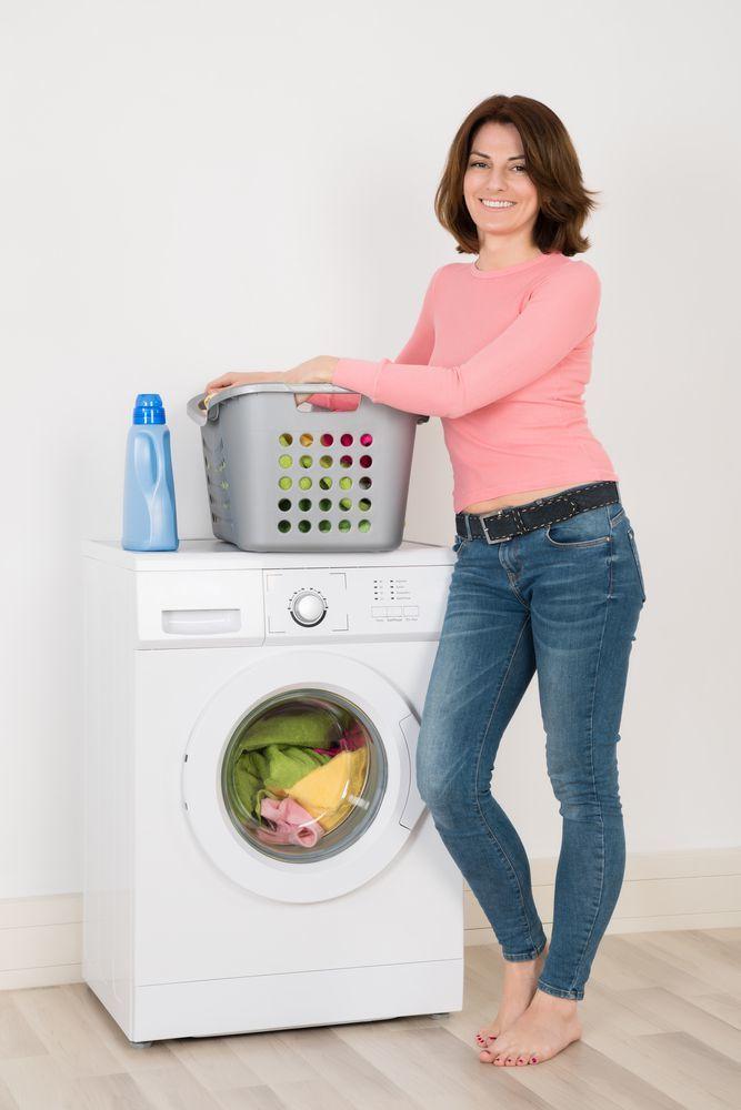 donna appoggiata alla lavatrice con focus sul detersivo per bucato
