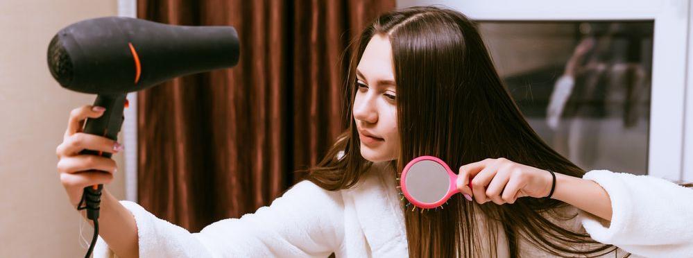ragazza durante l'asciugatura dei capelli con phon professionale