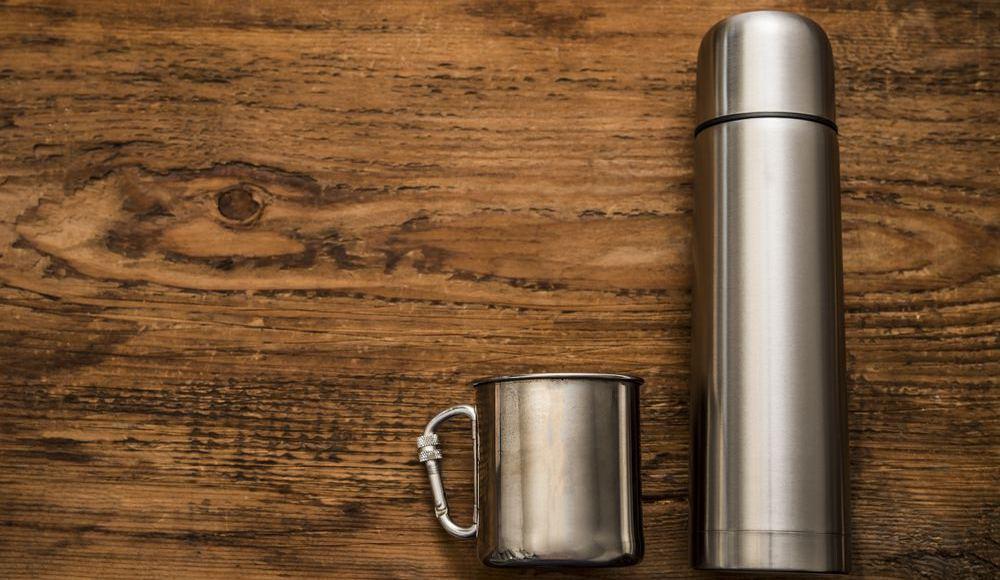 borraccia termica poggiata sul tavolo con accanto una tazza entrambe in acciaio inox