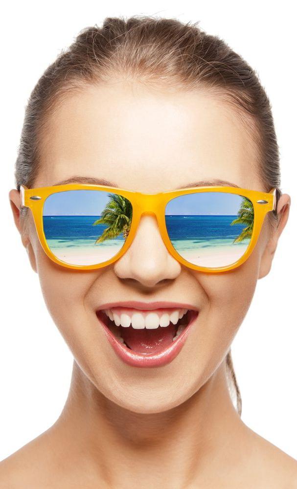 ragazza sorridente con occhiali da sole polarizzati con lenti a specchio con riflesso di una spiaggia