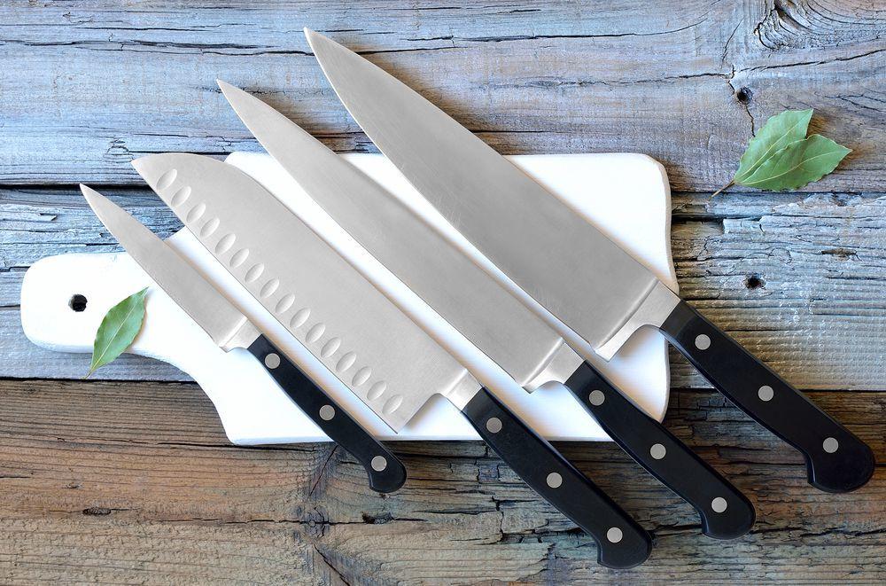 quattro coltelli da cucina su di un tagliere