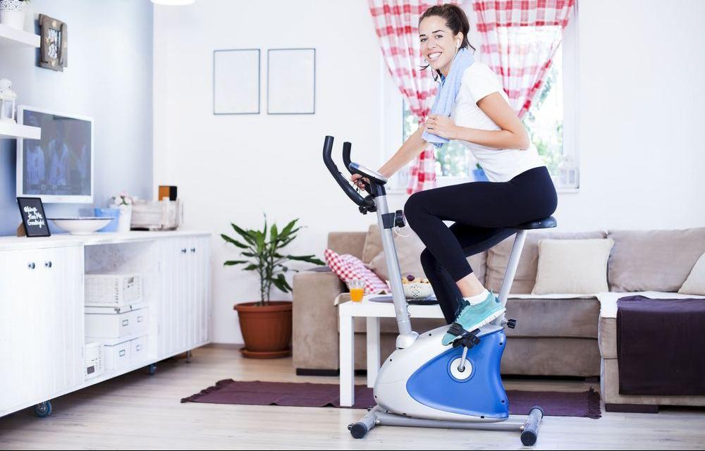 donna che si allena su cyclette in casa