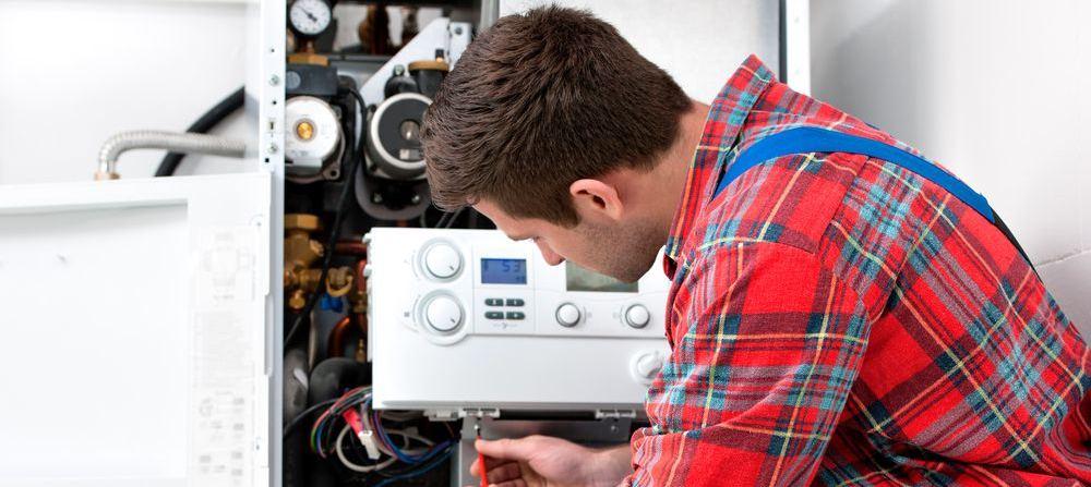 idraulico mentre effettua revisione ad una caldaia a condensazione