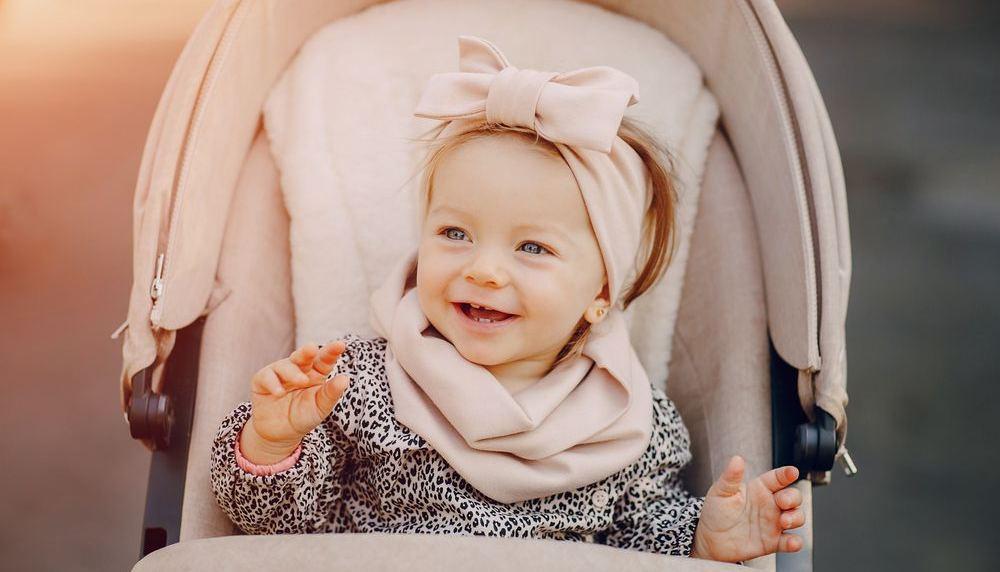 neonato sorridente in carrozzina