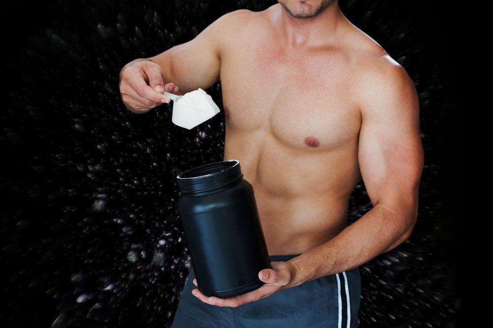 bodybuilder con in mano una generica confezione di proteine in polvere