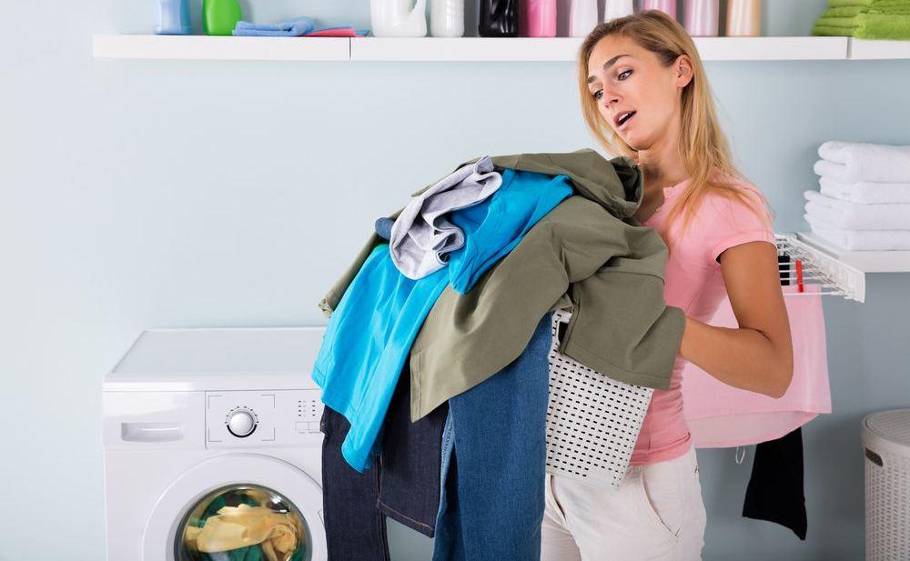 donna con indumenti vicino asciugatrice