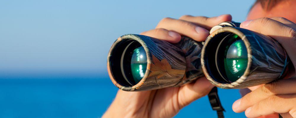 uomo durante osservazione di un paesaggio con binocolo
