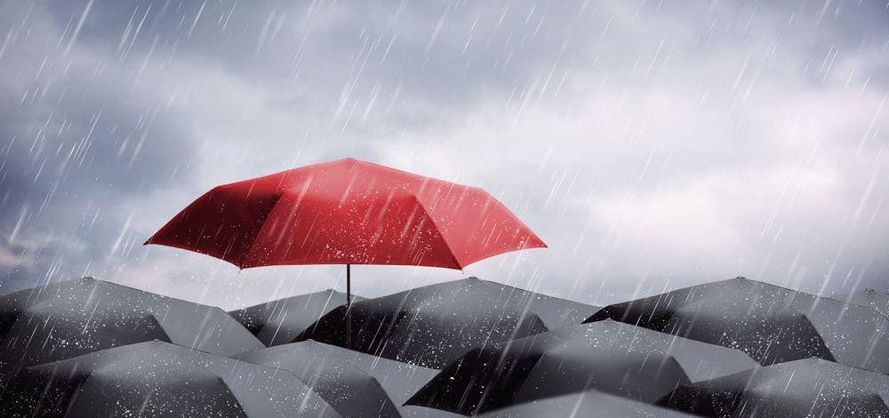 singolo ombrello antivento pieghevole rosso che spicca tra altri di colore scuro durante un temporale