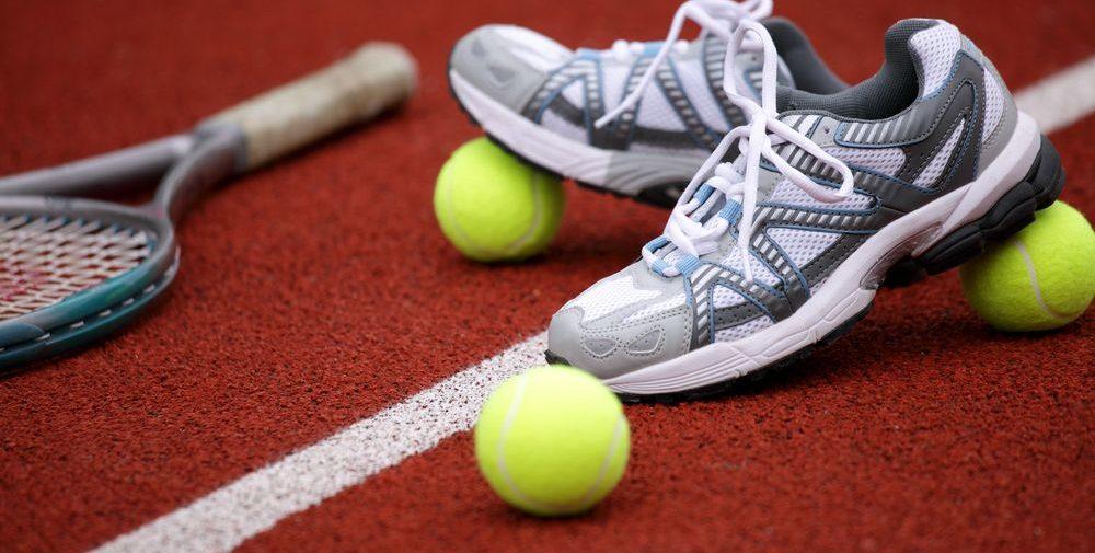fotografia di scarpe da tennis su campo con palline e racchetta