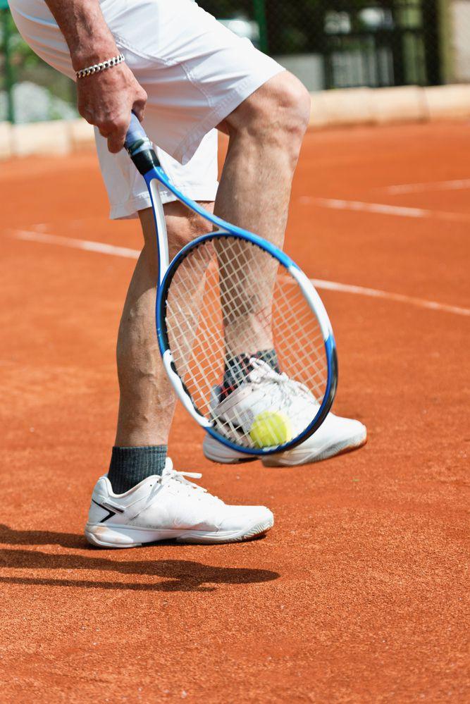 tennista mentre alza la pallina dalle scarpe da tennis con la sua racchetta