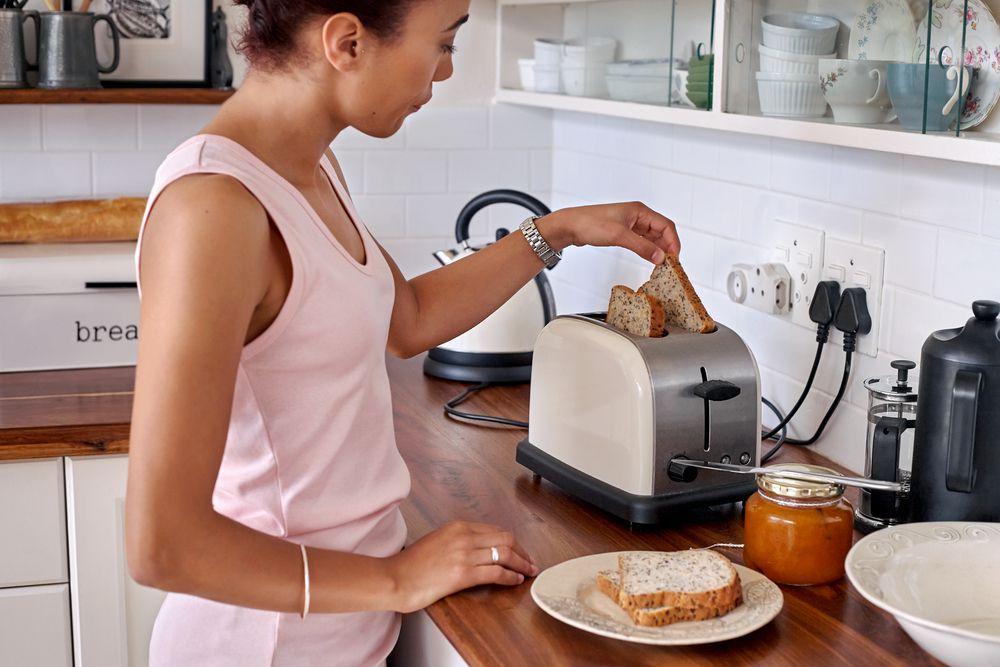 giovane mentre prepara una colazione con tostapane